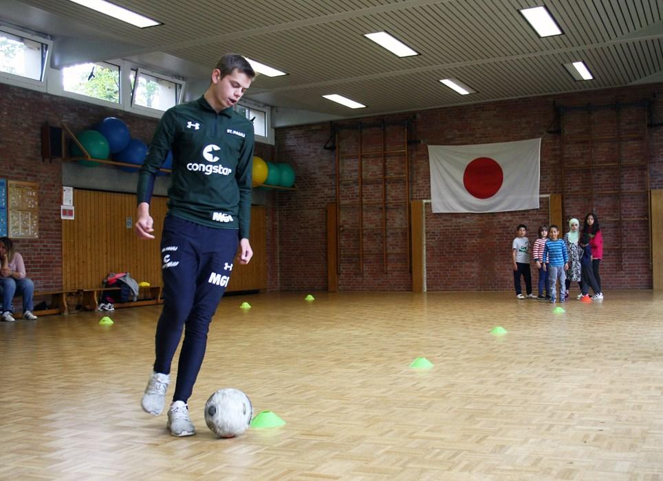 FCSP-Rabauken-Trainer Max macht die Übung vor, die Kinder schauen gespannt zu.