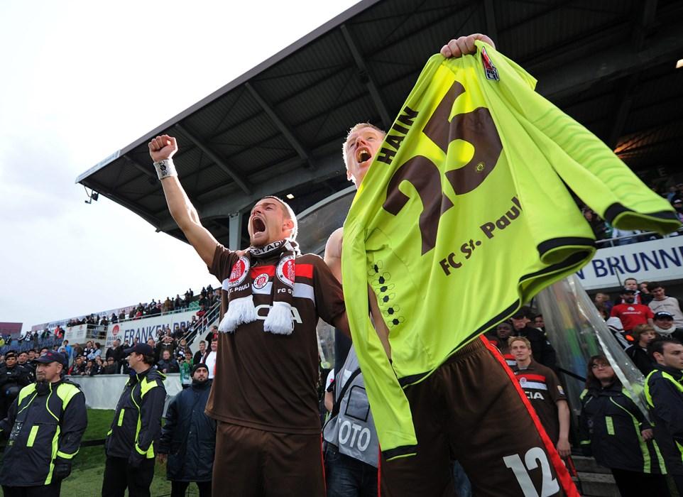 Gemeinsam mit Deniz Naki bejubelt Timo Schultz den Bundesliga-Aufstieg und hält dabei das Trikot von Matze hoch.